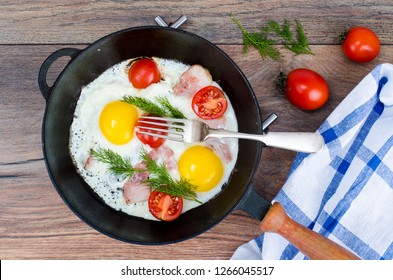 Frying pan with fried eggs, bacon and tomatoes. Studio Photo