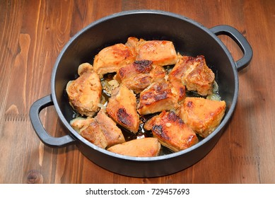 Frying pan with fried meat on a dark wooden table.