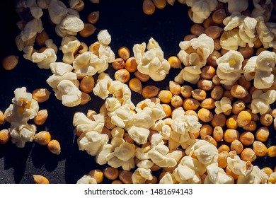 A frying pan full of half-made popcorn. Some have already exploded and the others are halfdone. The appearance of the lid is old and worn by use.