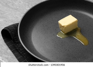 Frying pan with melting butter on grey table, closeup