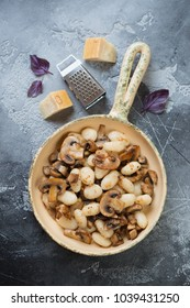Frying pan with potato gnocchi, roasted mushrooms and onion on a grey concrete background, view from above, vertical shot