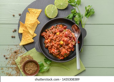 Frying pan with tasty chili con carne on wooden table