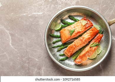 Frying pan with tasty cooked salmon on table, top view