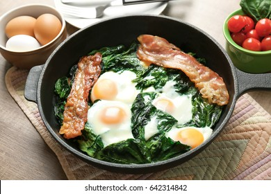 Frying pan with tasty eggs, spinach and bacon on wooden table
