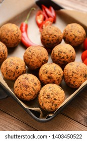 Frying pan with tasty falafel balls on wooden table, closeup