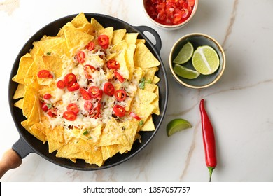 Frying pan with tasty nachos, cheese and chili on light table