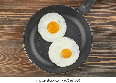 Frying pan with tasty over easy eggs on wooden table