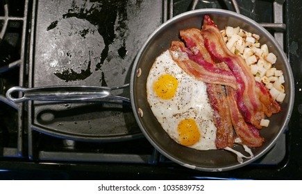 Frying pan with two eggs, bacon and cubed potatoes