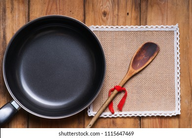 Frying pan, wooden spoon and tablecloth on the table background