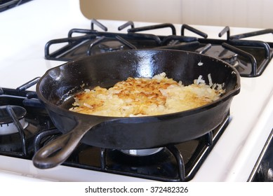 Frying potato hashbrowns in a black iron skillet on a gas stove.