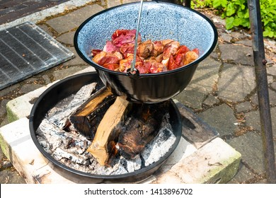 Frying the raw beef in a cauldron over an open wood fire to prepare the Hungarian cauldron goulash.
