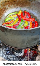 Frying red and green chilies on open fire