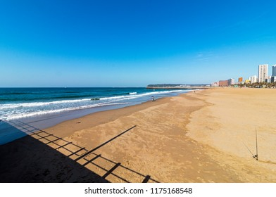 A fside view of the beach sand leading to the blue ocean water with buildings in the far distance