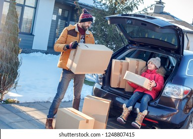 Fsther and daughter moving to new apartment together during winter standing outdoors near car taking boxes from trunk smiling happy