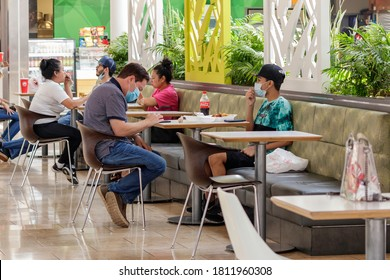 Ft. Lauderdale, Florida / USA - 8/28/2020: Father and son at a plantation mall food court eating lunch during the covid 19 coronavirus pandemic wearing face mask personal protective covering.