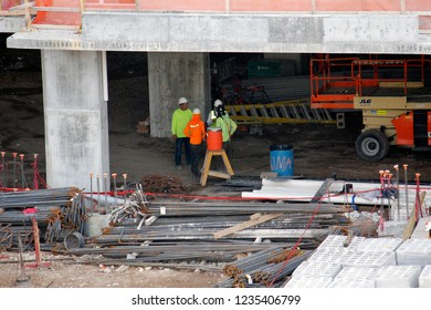 Ft. Lauderdale, Florida / USA - November 19 2018: High rise construction workers with concrete, re bar, steel, safety equipment, cranes, power tools, hammers, water cooler, outside in the hot sun.