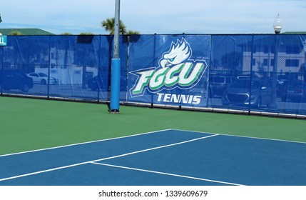 Ft. Myers, FL/USA: March 1, 2019 – Sign showing Florida Gulf Coast University logo on fence at college tennis court features its nickname The Eagles.