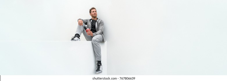 Ftiness sport man drinking smoothie workout banner relaxing at home in gym jogging pants activewear outdoor. Athlete sitting on white background.