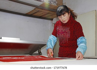 FUCHENG - DECEMBER 8: The female workman was framing paper-cut works, on december 8, 2013, fucheng, hebei province, China.