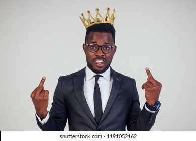 fuck you I'm business king. Confident businessman in a black classic suit with a tie and glasses put on a crown on head and shows middle finger in white background in studio. vanity and selfishness