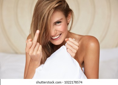 Fuck you. Happy woman with long hair, cheerful expression, shows middle finger, has fun at comfortable bed, gestures in bedroom. Attractive young female shows fuck sign. Body language concept