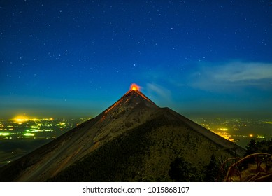 Fuego Volcano erupting with lava at night with stars and town in background in Guatamala