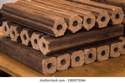Fuel briquettes folded in rows on a table. Wooden  briquettes are an environmentally friendly fuel source that are used to start a fire. They are made by pressing of dry sawdust.