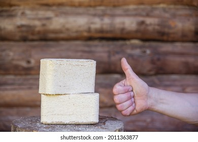 Fuel briquettes from pressed sawdust on a wood background. Human hand with a raised thumb.