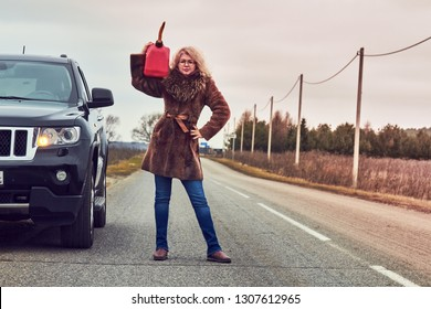 The fuel in the car has run out. A blond, curly girl stands next to a black car, wearing glasses, blue jeans and a brown coat on a deserted road with red canister on the shoulder.