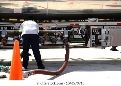 Fuel delivery driver checks the valves as gas is delivered from his tanker to the underground storage tanks at a local gas station.