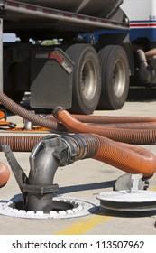 Fuel drop hose transferring gasoline into filling station gas reservoir