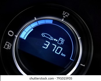 Fuel economy gauge with indication of mileage remaining to refueling. Close-up fragment of car dashboard.