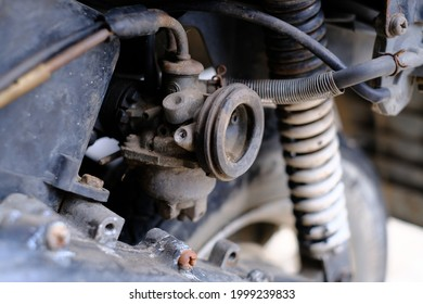 Fuel leaking out of the old carburetor. Common carburetor fuel leaks. Close-up of dirty carburetor in old motorcycle engine. The problem of a carburetor that leaks fuel. Engine repair.
