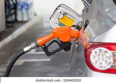 fuel nozzle is filling oil to silver car at petroleum station,  refill     oil fuel.  concept : Use of mobile phones at petrol stations do not cause fires