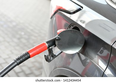 Fuel nozzle in the gas tank of a car close-up photo. Gas station Refueling concept. copispeis