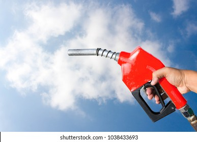 Fuel nozzle red handles hold the start of energy business travel business on sky background