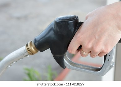 Fuel nozzle in womens hand - refilling gasoline