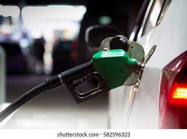 Fuel nozzles adding gasoline fuel in car at a pump gas station