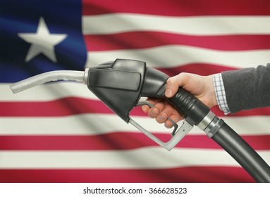Fuel pump nozzle in hand with flag on background - Liberia