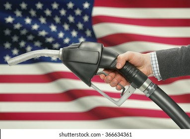 Fuel pump nozzle in hand with flag on background - United States - USA