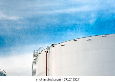 Fuel storage tank with a cloudy blue sky