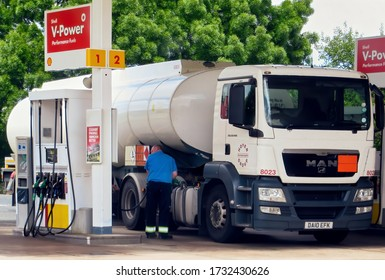 Fuel Tanker Truck Driver Getting Petrol for His Huge Vehicle at Small Gas Station Before Resuming March Toward Airport to Deliver Special Aviation Fuel (1863 Code on Orange Plate). CHEAM, UK -MAY 2015