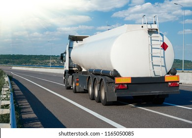 fuel truck rides on road, white blank color, rear view, one object on highway