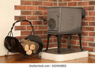 Fuel wood, wood for fireplace, in the background of the old wood burning stove, fireplace. Brick old wall background.