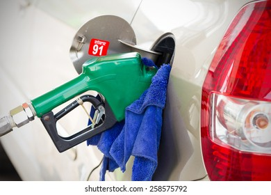 Fueling nozzle inserted into petrol tank at gas station for gasoline filling with cleaning cloth.