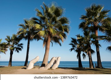 """Fuengirola,Andalucia/Spain-February 4, 2019 : Open hand sculpture around palm trees by the sculptor Charo Garcia, at the """"Park of life"""" on the beach """" Los Boliches"""" at Fuengirola ."""