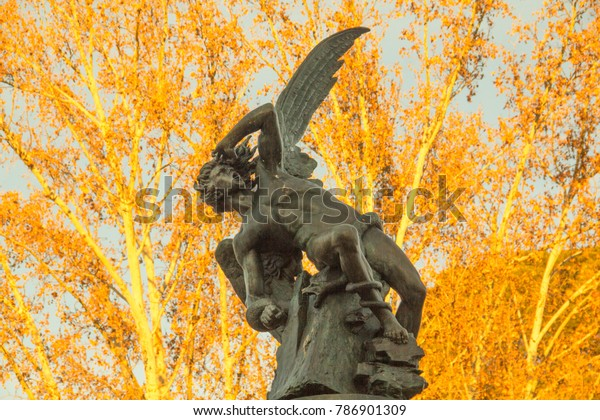 The Fuente del Ángel Caído (Fountain of the Fallen Angel) statue in Retiro Park, Madrid, Spain, representing the devil or Satan falling from heaven.