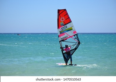 FUERTEVENTURA, CANARY ISLANDS - JULY 2019 - Unidentified windsurfer in action at Playa Barca in Costa Calma