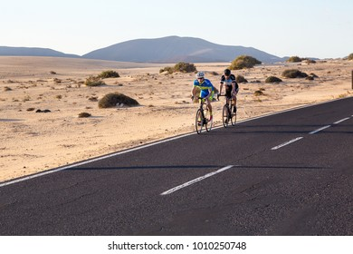 Fuerteventura, Canary Islands, Spain - 12/21/2017. Cyclists on a road in a Corralejo Natural Park. Bicycling biking tour travel trip. Two guys riding a bike in a desert highway