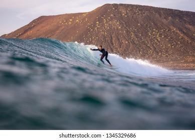 Fuerteventura - March 01, 2019: surfer riding waves on the island of fuerteventura in the Atlantic Ocean